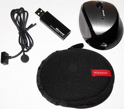 The complete Memory Mouse ensemble: mouse, wireless receiver, charging cable, and carrying case.